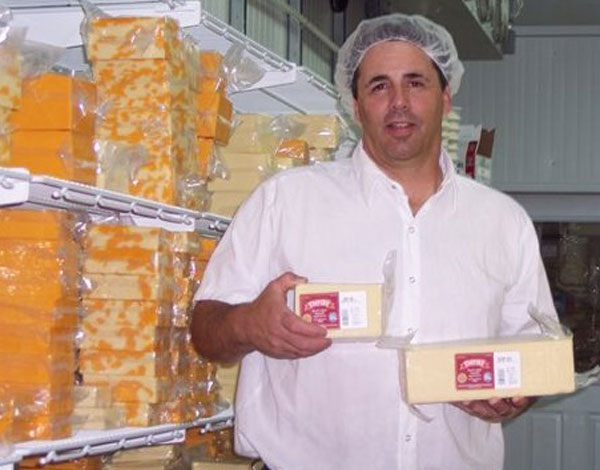 Cheesemaker Mark Erwin with two first-place cheddars. (Photo by Rebecca Crosgrey.